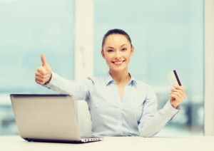 35562430 - business, investing and technology concept - businesswoman with laptop and credit card in office showing thumbs up
